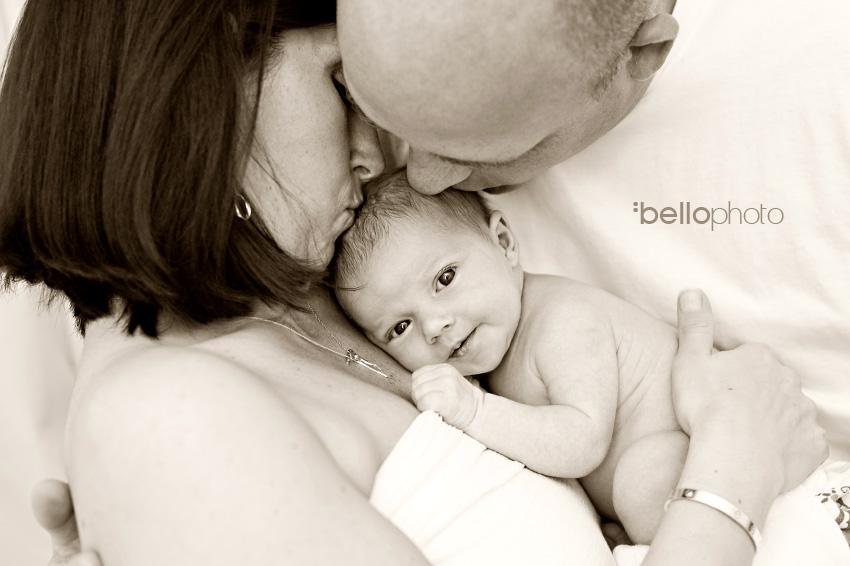 newborn getting kisses