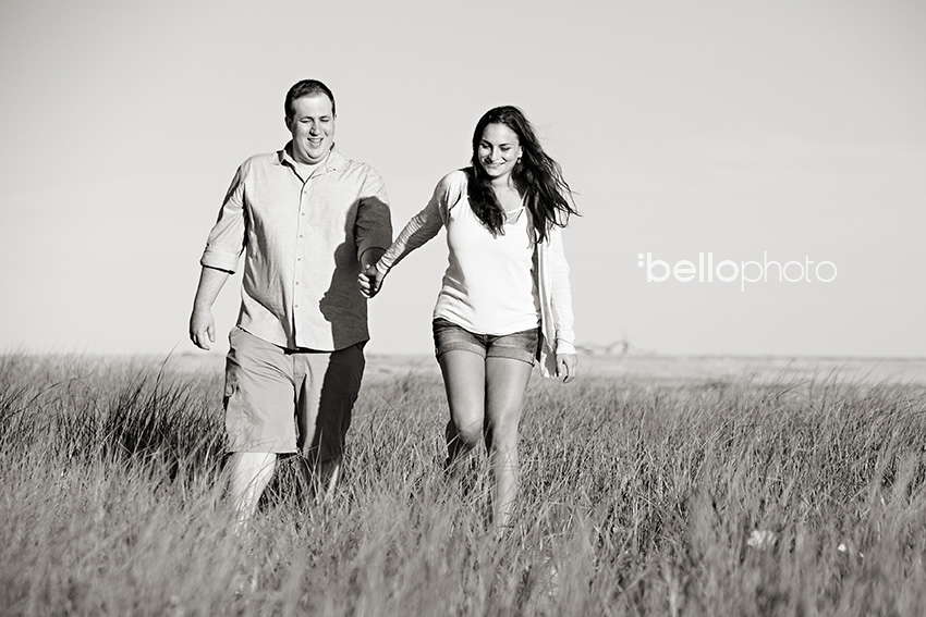 newly engaged couple walking in beach grass