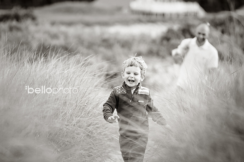 boy running through beach grass